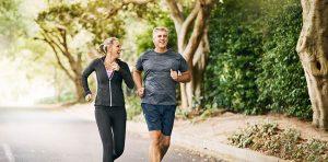 A couple is jogging through a park path