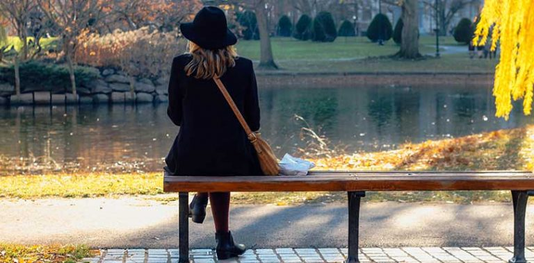A woman sitting on a bench in a park
