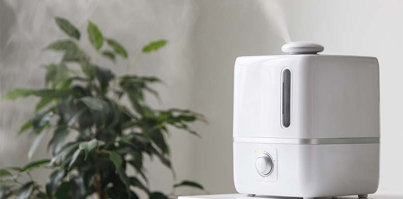 A white humidifier sitting next to a plant.